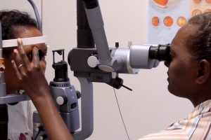 Ophthalmologist examines a patient's eye for diabetic retinopathy, Solomon Islands